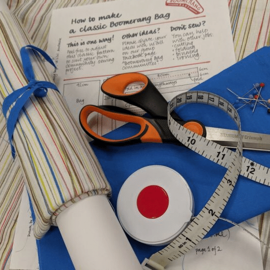 Sewing basics on a table: scissors, tape measure, pins with coloured heads, fabric and a pattern that says how to make a classic Boomerang Bag.